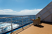 Woman relaxes on deck of the Aranui 5 (Aranui Cruises) passenger cargo ship, at sea between the Marquesas Islands and the Tuamotu Islands, French Polynesia, South Pacific