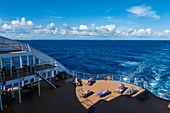 People relax on the aft sundeck of the Aranui 5 (Aranui Cruises) passenger cargo ship, at sea between the Tuamotu Islands and the Leeward Islands, French Polynesia, South Pacific