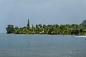 Menschen schwimmen im Wasser mit einer von Bäumen gesäumten Küste dahinter, Teahupoo, Tahiti, Windward Islands, Französisch-Polynesien, Südpazifik