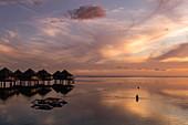 Silhouette von Frau im Wasser neben Auslegerkanu und Überwasserbungalows des Tahiti Ia Ora Beach Resort (managed by Sofitel) bei Sonnenuntergang, nahe Papeete, Tahiti, Windward Islands, Französisch-Polynesien, Südpazifik