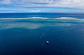 Aerial view of a tour boat on the southwest coast of Tahiti-Iti with reef in the distance, Pointe Puforatiai, Tahiti, Windward Islands, French Polynesia, South Pacific
