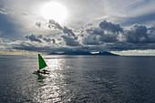 Luftaufnahme eines Ausleger Segelkanus bei Sonnenuntergang mit Insel Moorea in der Ferne, Nuuroa, Tahiti, Windward Islands, Französisch-Polynesien, Südpazifik