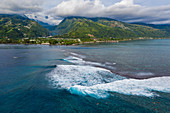 Aerial view of surfers on wave on reef with coast and mountains behind, Nuuroa, Tahiti, Windward Islands, French Polynesia, South Pacific