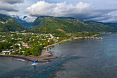 Aerial view of outrigger canoe with sails on the beach with coastline and mountains behind, Nuuroa, Tahiti, Windward Islands, French Polynesia, South Pacific