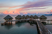 Aerial view of the overwater bungalows at Tahiti Ia Ora Beach Resort (managed by Sofitel) at sunset, near Papeete, Tahiti, Windward Islands, French Polynesia, South Pacific