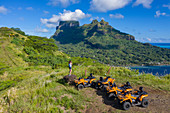 Aerial view of quad ATVs on hill with Mount Otemanu behind, Bora Bora, Leeward Islands, French Polynesia, South Pacific