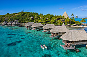 Aerial view of how breakfast is brought by pirogue outrigger canoe to an overwater bungalow of the Sofitel Bora Bora Private Island Resort in the Bora Bora Lagoon, Bora Bora, Leeward Islands, French Polynesia, South Pacific