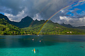 Aerial view of outrigger racing canoes in the Moorea Lagoon with rainbow and mountain backdrop, Avamotu, Moorea, Windward Islands, French Polynesia, South Pacific