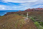 Aerial view of white cross on hill with passengers from passenger freighter Aranui 5 (Aranui Cruises), Tekoapa, Ua Huka, Marquesas Islands, French Polynesia, South Pacific