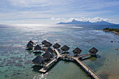 Aerial view of overwater bungalows of the Tahiti Ia Ora Beach Resort (managed by Sofitel) with Moorea Island in the distance, near Papeete, Tahiti, Windward Islands, French Polynesia, South Pacific
