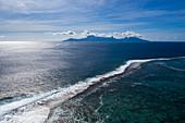 Luftaufnahme des Riffs das die Lagune vom Südpazifik trennt mit Insel Moorea in der Ferne, nahe Papeete, Tahiti, Windward Islands, Französisch-Polynesien, Südpazifik