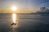 Aerial view of an outrigger canoe in the lagoon at sunset with Moorea Island in the distance, near Papeete, Tahiti, Windward Islands, French Polynesia, South Pacific