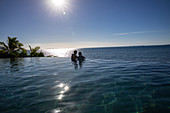 People relaxing in the infinity pool at Malamala Island Beach Club, Mala Mala Island, Mamanuca Group, Fiji Islands, South Pacific