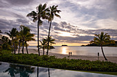 Swimming pool, coconut trees and a couple walking on the beach at Six Senses Fiji Resort at sunset, Malolo Island, Mamanuca Group, Fiji Islands, South Pacific