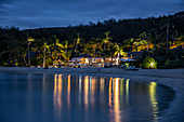 Beach and reflection of coconut trees and Six Senses Fiji Resort in the bay at dusk, Malolo Island, Mamanuca Group, Fiji Islands, South Pacific