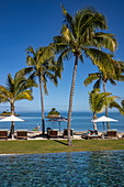Swimming pool, sun loungers and coconut trees at Six Senses Fiji Resort, Malolo Island, Mamanuca Group, Fiji Islands, South Pacific