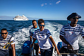 Four crew members of the cruise ship MV Reef Endeavor (Captain Cook Cruises Fiji) on the transfer tender boat, near Yangetta Island, Yasawa Group, Fiji Islands, South Pacific