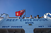 Crew waves goodbye from the deck of the cruise ship MV Reef Endeavor (Captain Cook Cruises Fiji), near Naviti Island, Yasawa Group, Fiji Islands, South Pacific