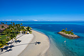 Aerial view of a Residence Villa accommodation in the Six Senses Fiji Resort with coconut trees, a beach and a family enjoying water sports activities next to a small offshore island, Malolo Island, Mamanuca Group, Fiji Islands, South Pacific