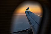 View out of window of a RwandAir Airbus A330-300 airplane with sun logo on winglet at sunrise, on the flight from Brussels International Airport (BRU) in Belgium to Kigali International Airport (KIG) Rwanda, Africa