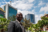 Dignified Rwandan man poses in front of parkland and high-rise office buildings in the city center, Kigali, Kigali Province, Rwanda, Africa