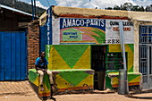 Young man sitting in front of a paint shop, Kigali, Kigali Province, Rwanda, Africa