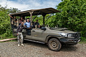 Group photo of happy visitors in safari vehicle operated by luxury resort tented Magashi Camp (Wilderness Safaris), Akagera National Park, Eastern Province, Rwanda, Africa