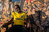 Young man with Rwanda jersey sits in front of mural with safari animal motif in a cafe, Kayonza, Eastern Province, Rwanda, Africa