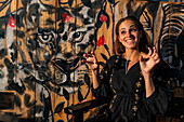 Young woman poses as a wild big cat in front of mural with safari animal motif in a cafe, Kayonza, Eastern Province, Rwanda, Africa