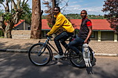 Two young men on bicycles with two killed rabbits in hand, Nyanza, Southern Province, Rwanda, Africa