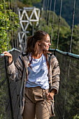 Young woman on suspension bridge of Canopy Walkway, Nyungwe Forest National Park, Western Province, Rwanda, Africa
