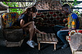 Two people play the traditional Igisoro board game in the lounge of the Paradis Malahide Hotel, Gisenyi, Western Province, Rwanda, Africa