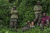 Ranger guides and young woman relax during a trekking excursion to the Sabyinyo group of gorillas, Volcanoes National Park, Northern Province, Rwanda, Africa
