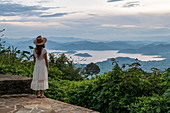 Young woman in summer dress and sun hat looks out over the Ruhondo Lake and the mountains from the terrace of the Virunga Lodge, near Kinyababa, Northern Province, Rwanda, Africa