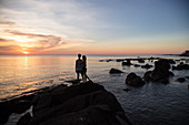Silhouette of young couple on rocks at Ong Lang Beach at sunset, Ong Lang, Phu Quoc Island, Kien Giang, Vietnam, Asia