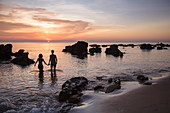 Silhouette of young couple holding hands on Ong Lang Beach at sunset, Ong Lang, Phu Quoc Island, Kien Giang, Vietnam, Asia
