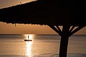 Silhouette von strohgedeckten Sonnenschirm und junger Frau auf Badeplattform im Wasser vor dem Ong Lang Beach, Ong Lang, Insel Phu Quoc, Kien Giang, Vietnam, Asien