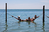 Couple relaxing in a floating hammock at Chez Carole Phu Quoc Resort on Ong Lang Beach, near Cua Can, Phu Quoc Island, Kien Giang, Vietnam, Asia
