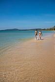 Young couple runs along the water's edge at the seemingly endless Van Beach, near Cua Can, Phu Quoc Island, Kien Giang, Vietnam, Asia