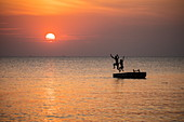 Silhouette of a young couple jumping from a bathing platform in front of Ong Lang Beach at sunset, Ong Lang, Phu Quoc Island, Kien Giang, Vietnam, Asia