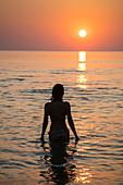 Silhouette von junger Frau im Wasser vor dem Ong Lang Beach bei Sonnenuntergang, Ong Lang, Insel Phu Quoc, Kien Giang, Vietnam, Asien