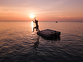 Luftaufnahme Silhouette von jungem Paar das bei Sonnenuntergang von einer Badeplattform am Ong Lang Beach springt, Ong Lang, Insel Phu Quoc, Kien Giang, Vietnam, Asien