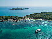 Aerial view of John's Tours No. 9 excursion boat and tourists snorkeling in clear water near beach with coconut palms, Dam Ngang Island, near Phu Quoc Island, Kien Giang, Vietnam, Asia
