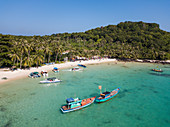 Aerial view of fishing boats moored in bay and beach with coconut palms, May Rut Island, near Phu Quoc Island, Kien Giang, Vietnam, Asia