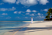 A woman dressed in white, tropical attire walks along a pristine beach. Antiugua, West Indies.