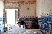 A maid is making the bed in a frescoed room, with light streaming from an open window. Shot inside Palacio Belmont, Lisbon, Portugal.
