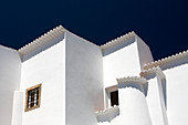 A white residential building set against a dark blue sky. The buildings are built in tradional style architecture in Algarve, Portugal.