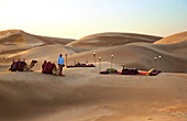 A beautiful desert picninc, set amidst the sanddunes, with a couple of camels and their minder in the foreground.\nShot in Saudi Arabia.