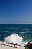 A huge break against a pool deck set with an ocean view, shot near Cascais in Portugal.