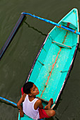 A young Malaysian boy looking into the camear from his turqoise boat, shot from above in Borneo, malaysia.